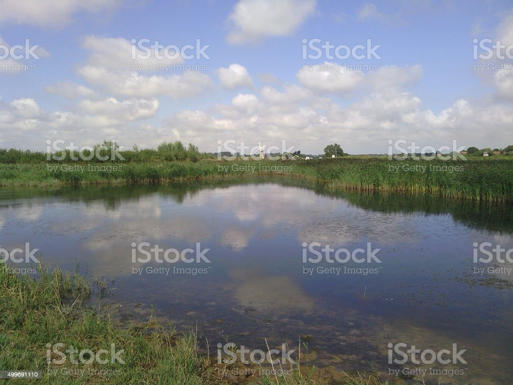 Norfolk Broads windmill and reflected sky stock photo