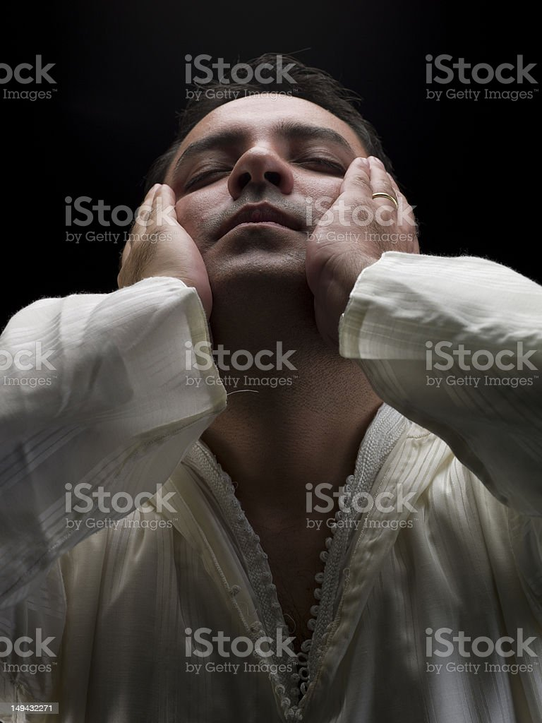 North African Muslim man praying, black background stock photo