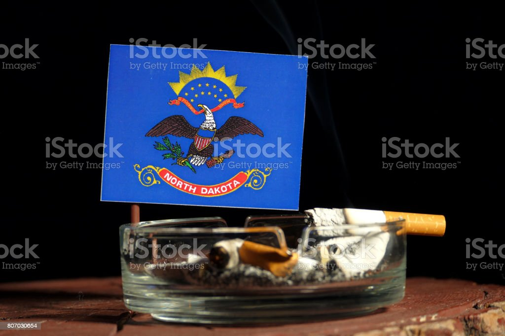 North Dakota flag with burning cigarette in ashtray isolated on black background stock photo