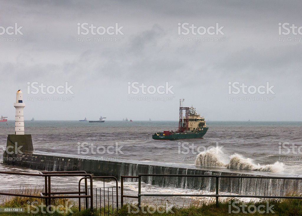 North Sea Oil Rig Supply Vessel at Harbour Lighthouse stock photo