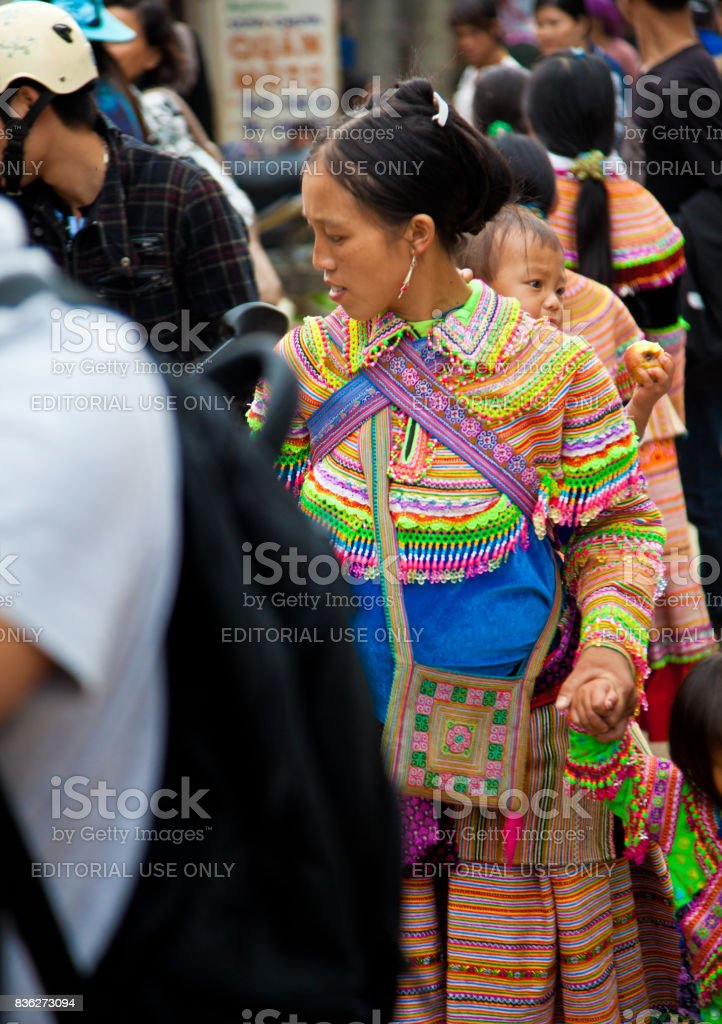 North Vietnamese woman in colorful native clothing with child on her back stock photo