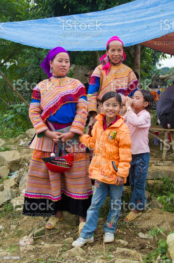 North Vietnamese women in colorful native clothing with children in Western garb stock photo
