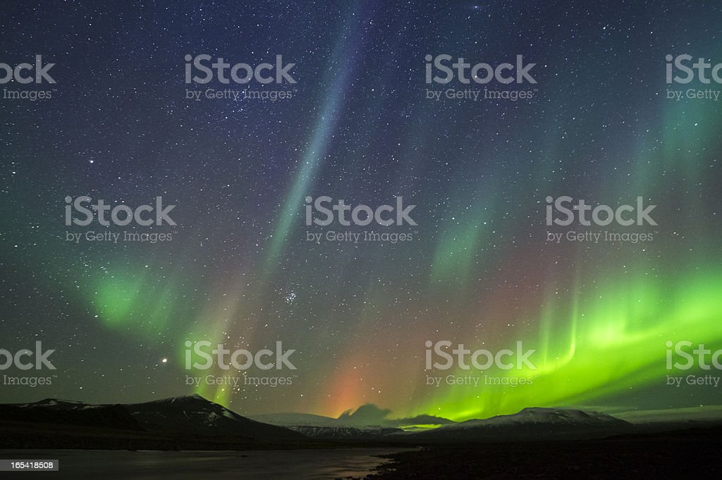 Northern lights against starry sky and silhouette mountains stock photo