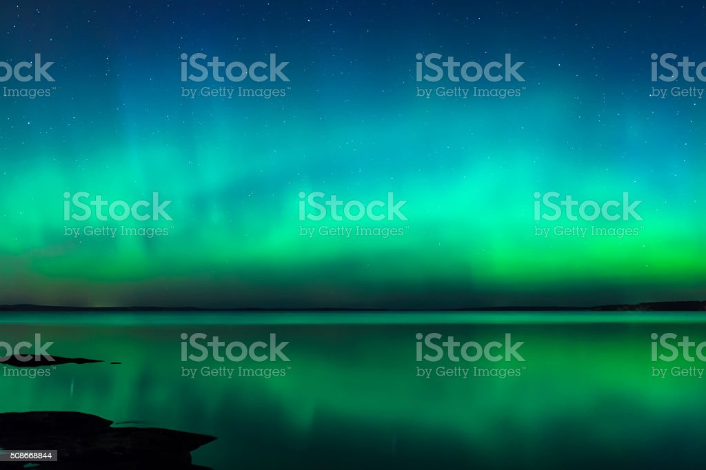 Northern lights over lake in finland stock photo