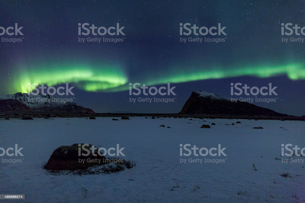 Northern Lights over the frozen Arctic fjord - solar storm stock photo