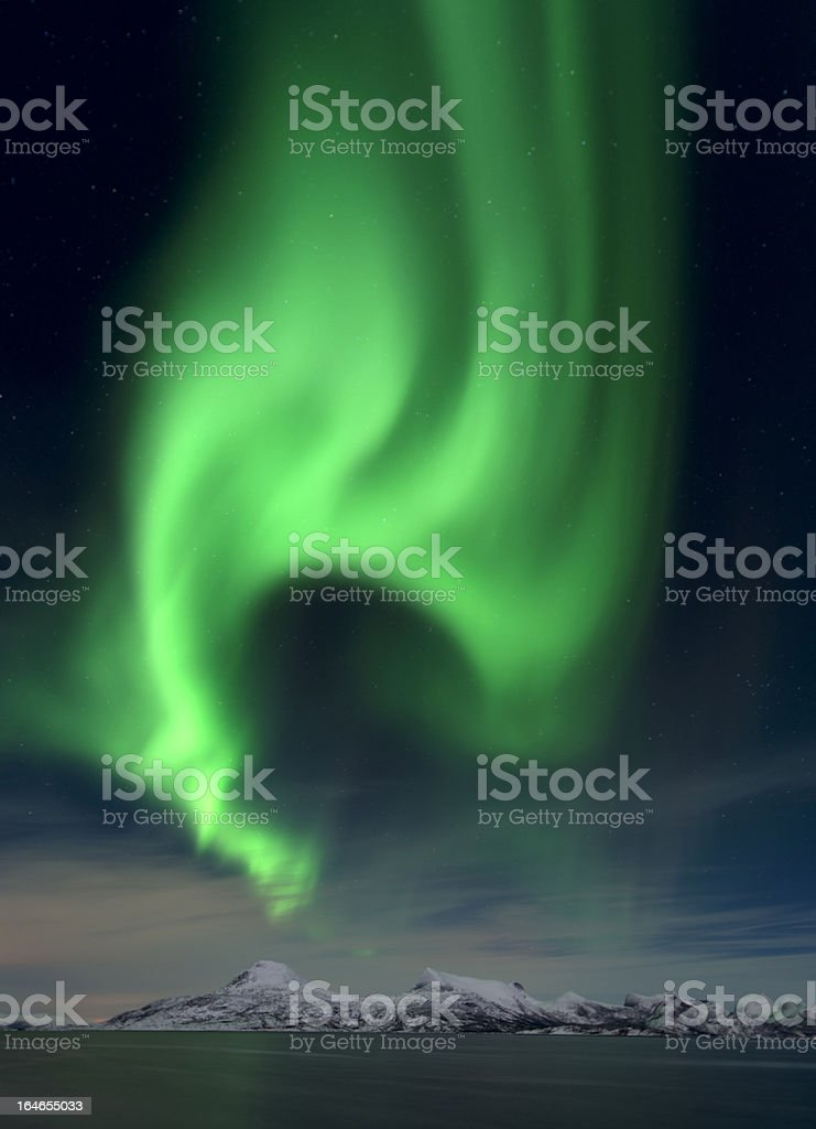 Northern lights (Aurora borealis) seaside with mountains in winter royalty-free stock photo