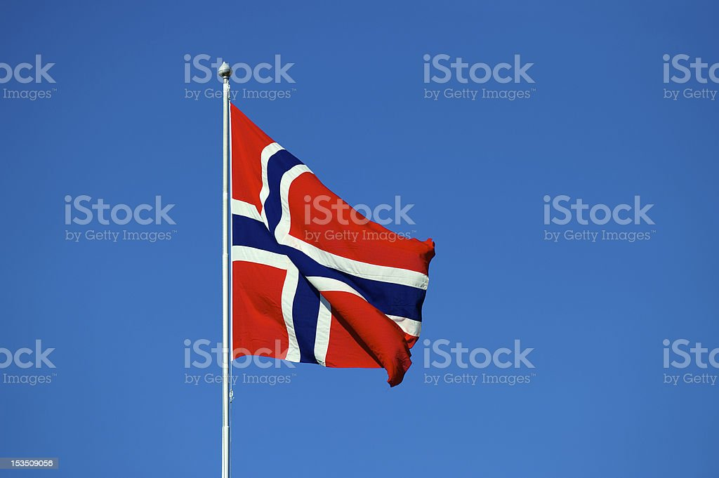 Norwegian flag in red, white and blue and clear skies stock photo