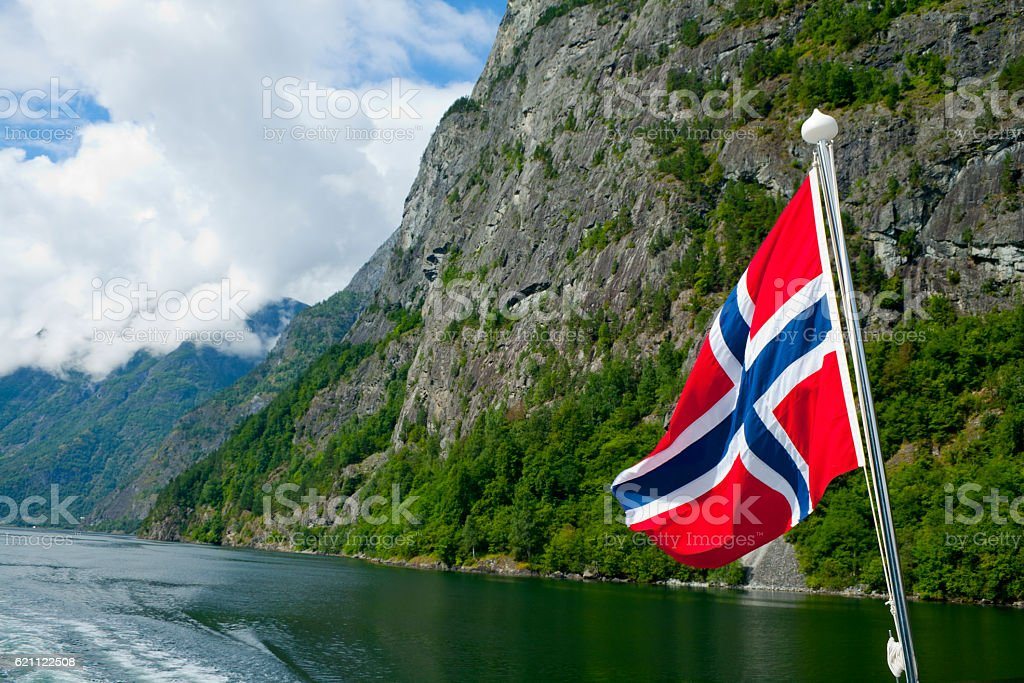 Norwegian flag waving in the fjords stock photo