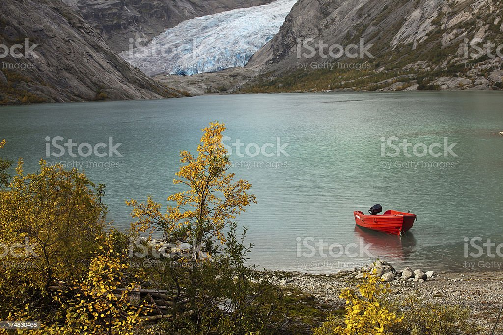 Norwegian glacier Nigadsbreen with lake and red boat royalty-free stock photo