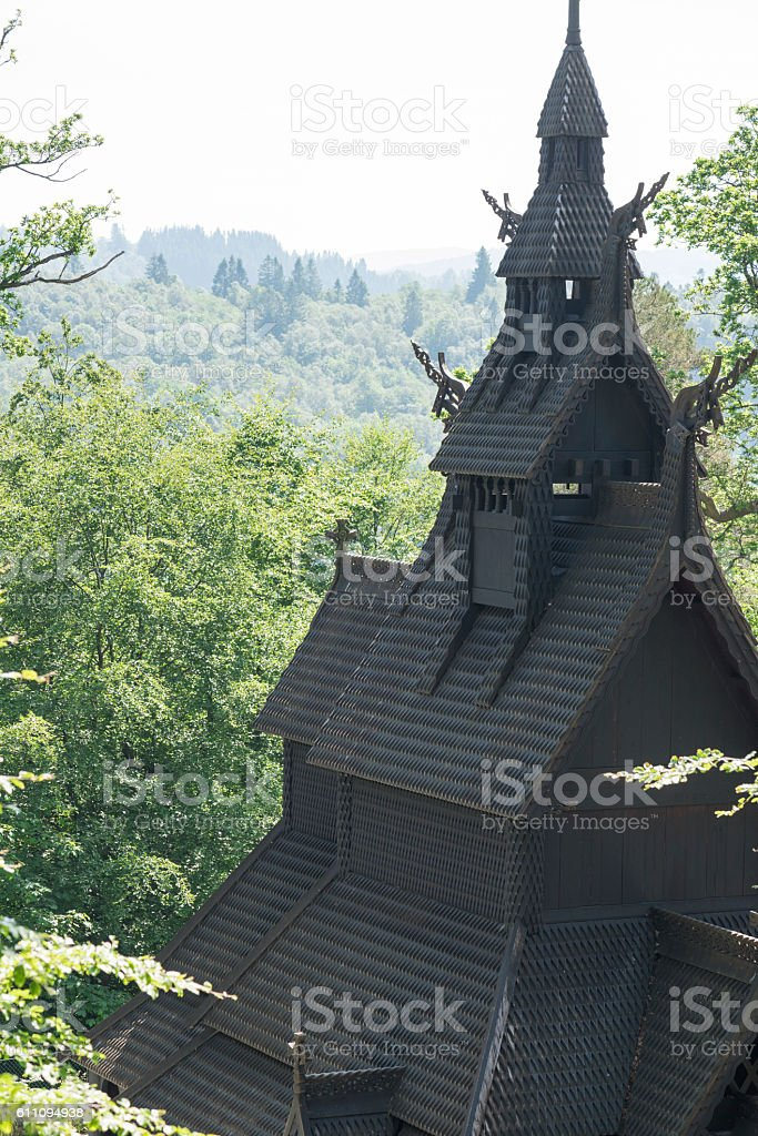 Norwegian stave church surrounded by lush foliage in summer stock photo