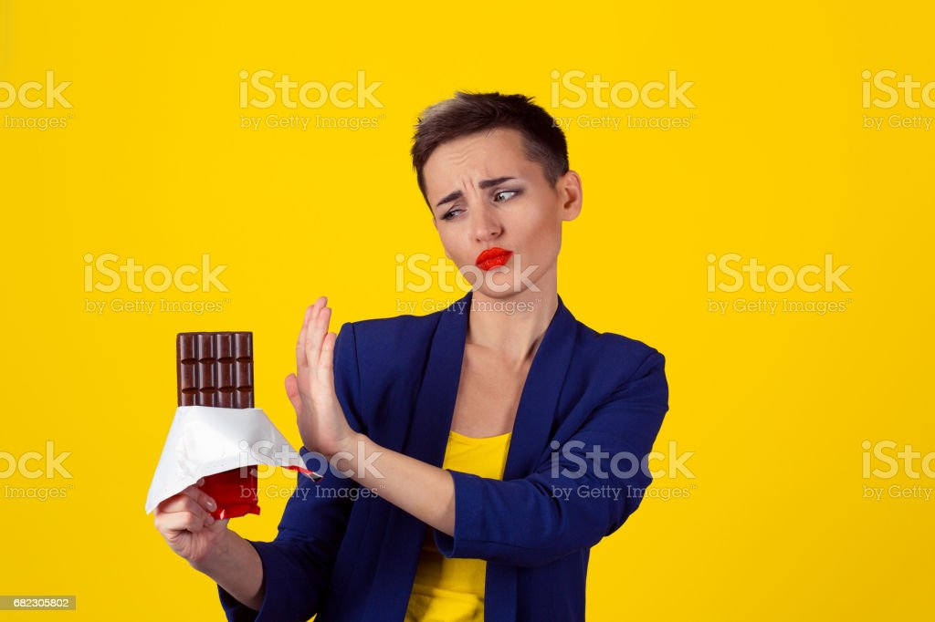 Not for me, thank you concept. Closeup Portrait of a young determined fit business woman girl refusing to eat chocolate isolated yellow background stock photo