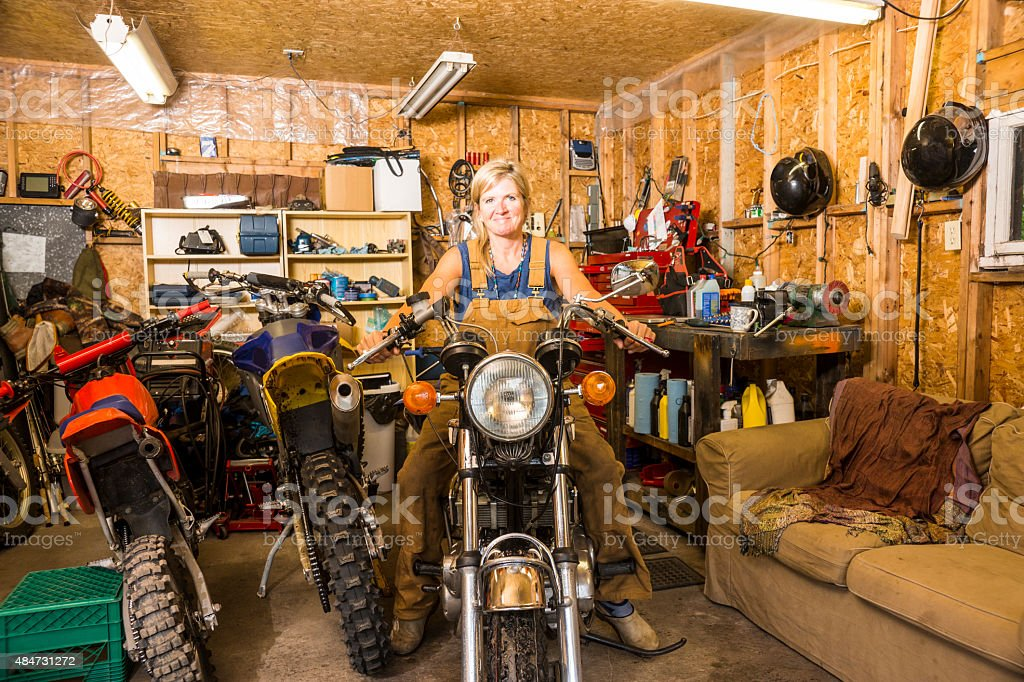 Not just for boys.  A woman in a motorcycle garage. stock photo