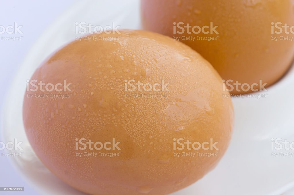Not peeled eggs with water drops on a brown shell. stock photo