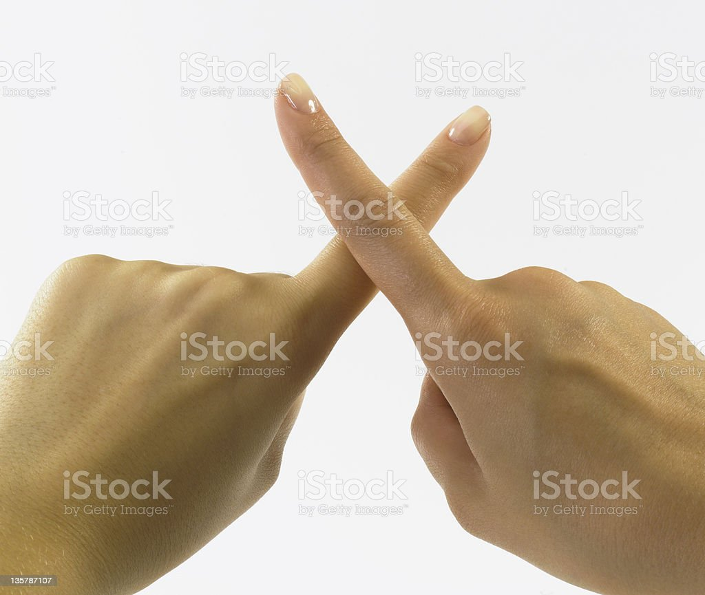 Not Permitted! Crossed female fingers denoting not permissible behavior stock photo