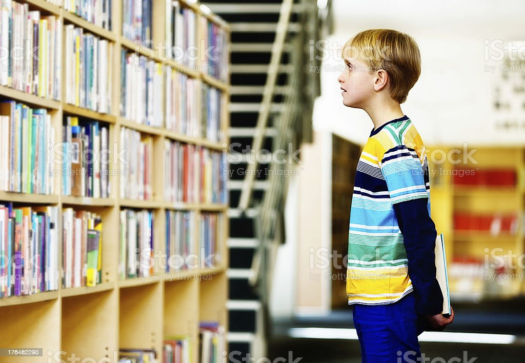 Not sure what to read, reluctant reader schoolboy in library stock photo