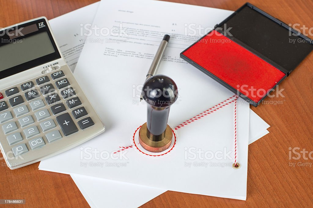 Notarial documents and seal with calculator on wooden desk royalty-free stock photo