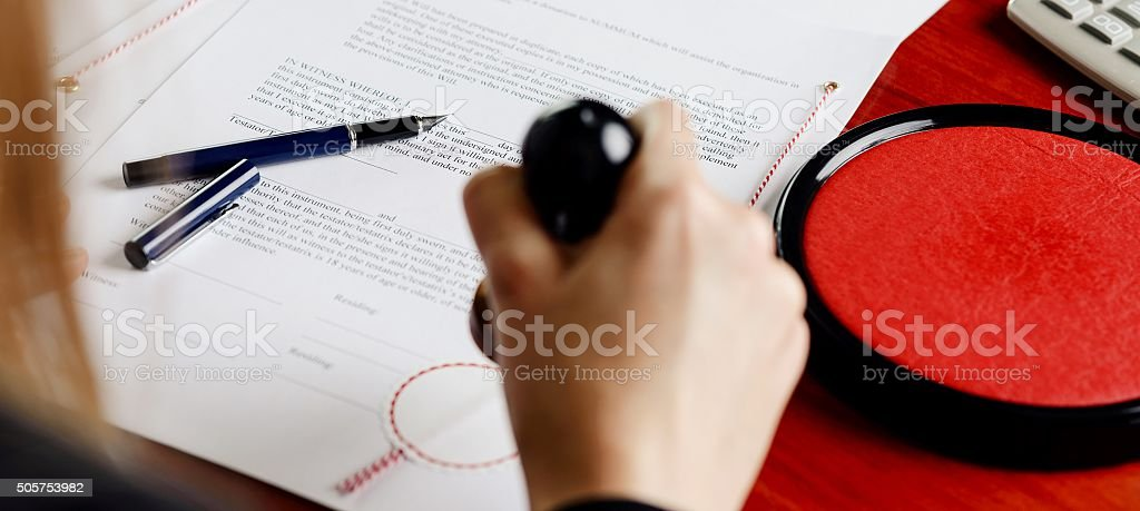 Notary public stamping document. stock photo