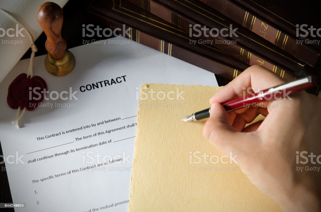 Notary signing a contract with fountain pen in dark room stock photo