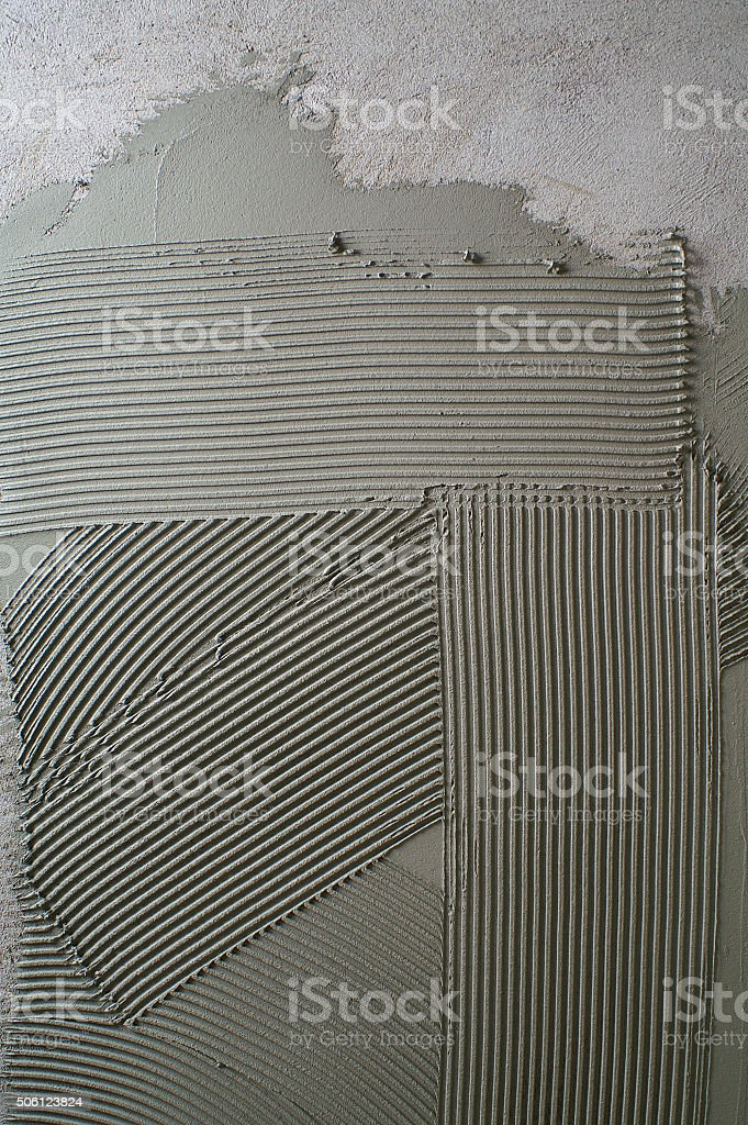 Notched troweling mortar onto a concrete wall in preparation stock photo
