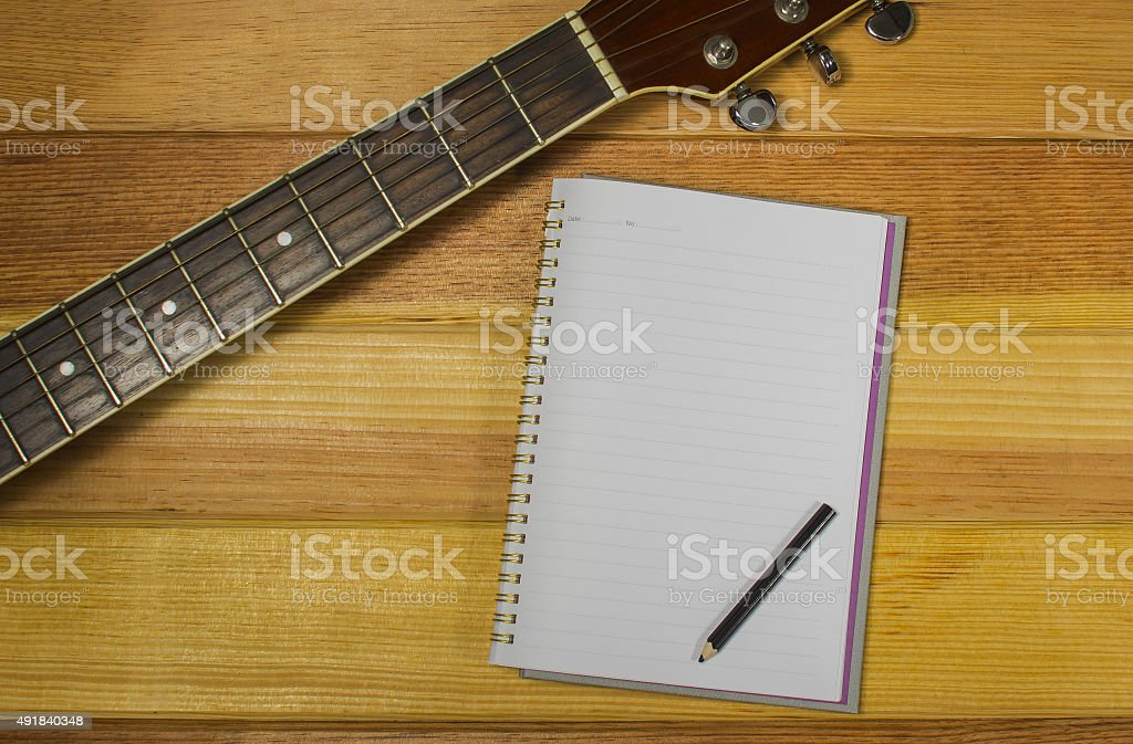 Note and guitar on the wooden floor. stock photo