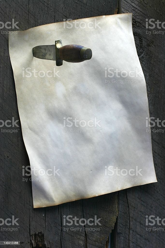 Note attached to wooden wall or door with dagger stock photo