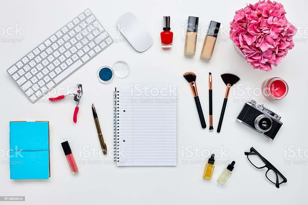 Note pad surrounded with various technologies and beauty product stock photo