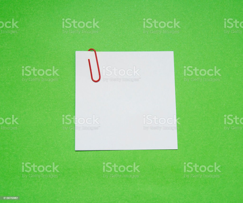 note with color paper clip isolated on green background stock photo