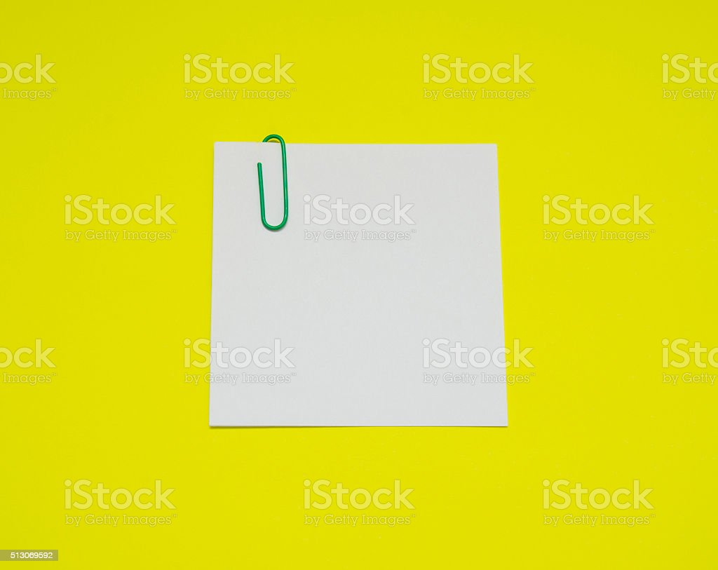 note with color paper clip isolated on yellow background stock photo