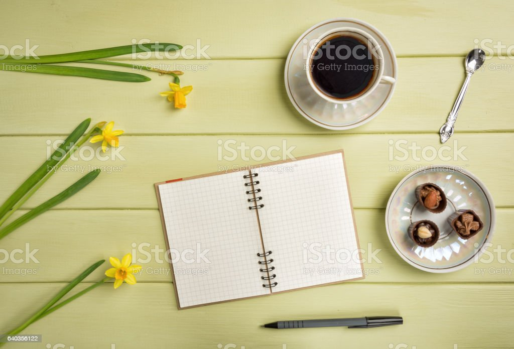Notebook, a pen, cup of coffee and flowers. Flat lay stock photo