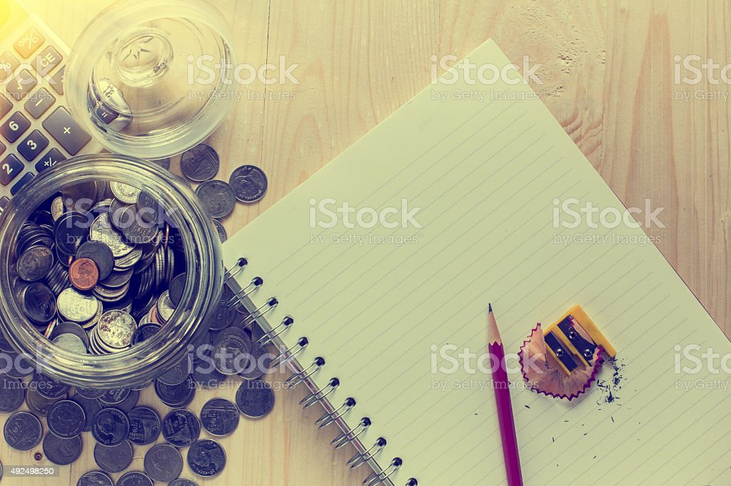 notebook  a pencil on wood floors and a piggy bank, stock photo