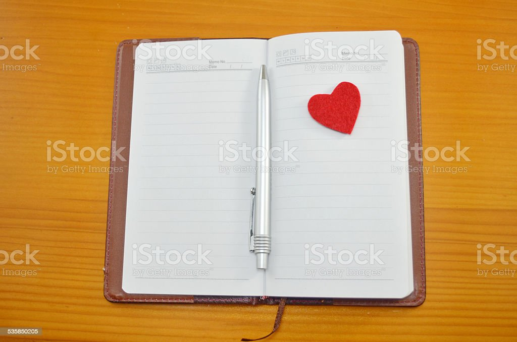 Notebook and a small red heart on a table royalty-free stock photo