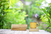 Notebook and coffee in yellow cup on wooden table