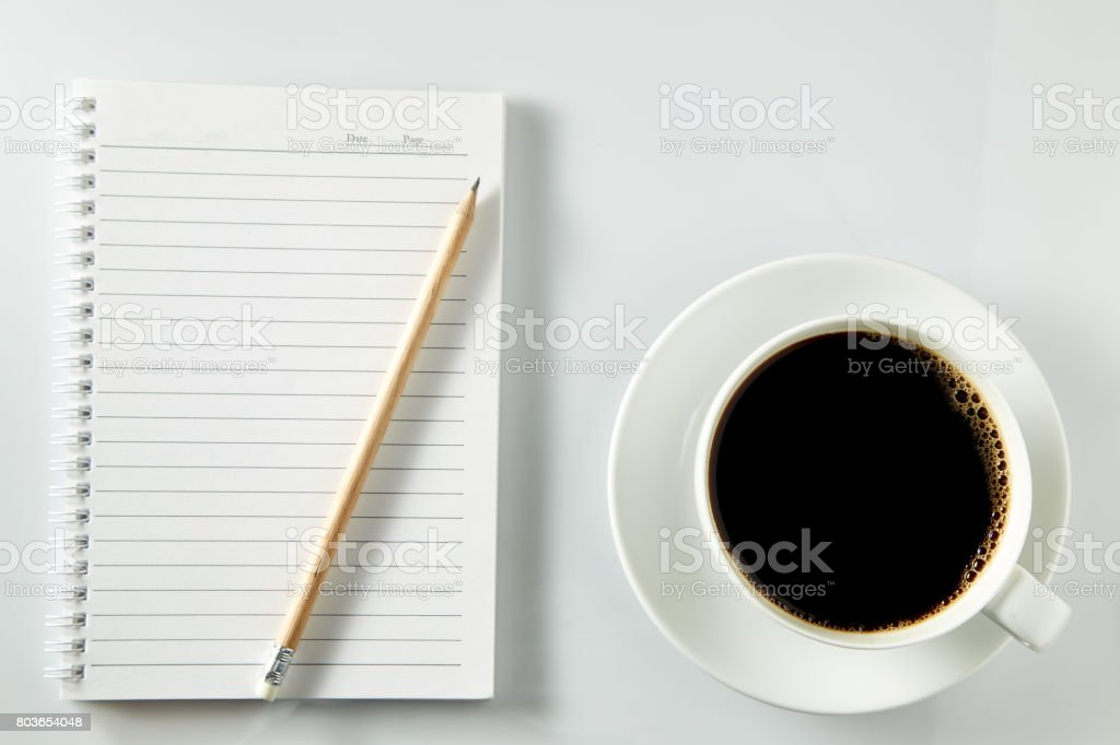 notebook and cup of coffee on wood table stock photo