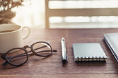 Notebook and cup of coffee with sunlight on desk office