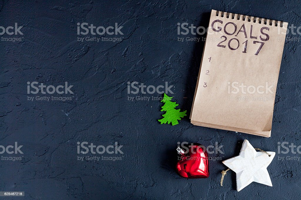 notebook and goals for new year dark background top view stock photo