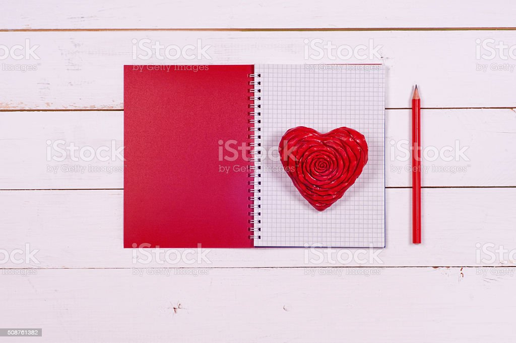 Notebook and heart on a white rustic background. Valentine's Day. stock photo