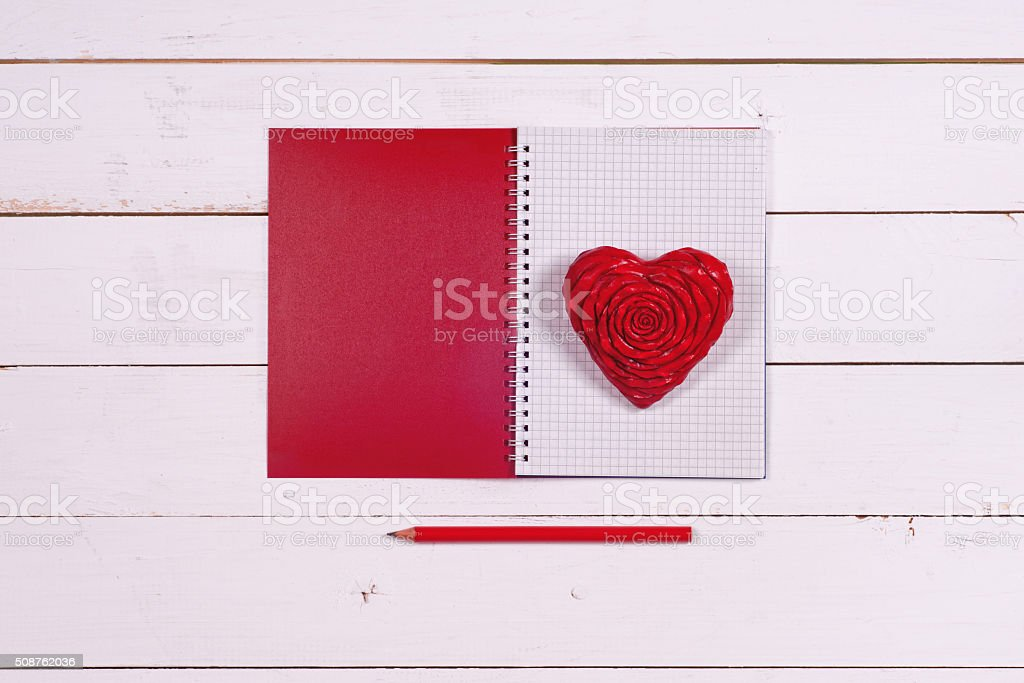 Notebook and heart on a white rustic background. Valentine's Day stock photo