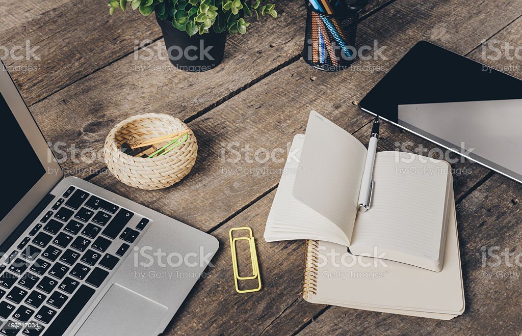Notebook and laptop on old wooden desk stock photo