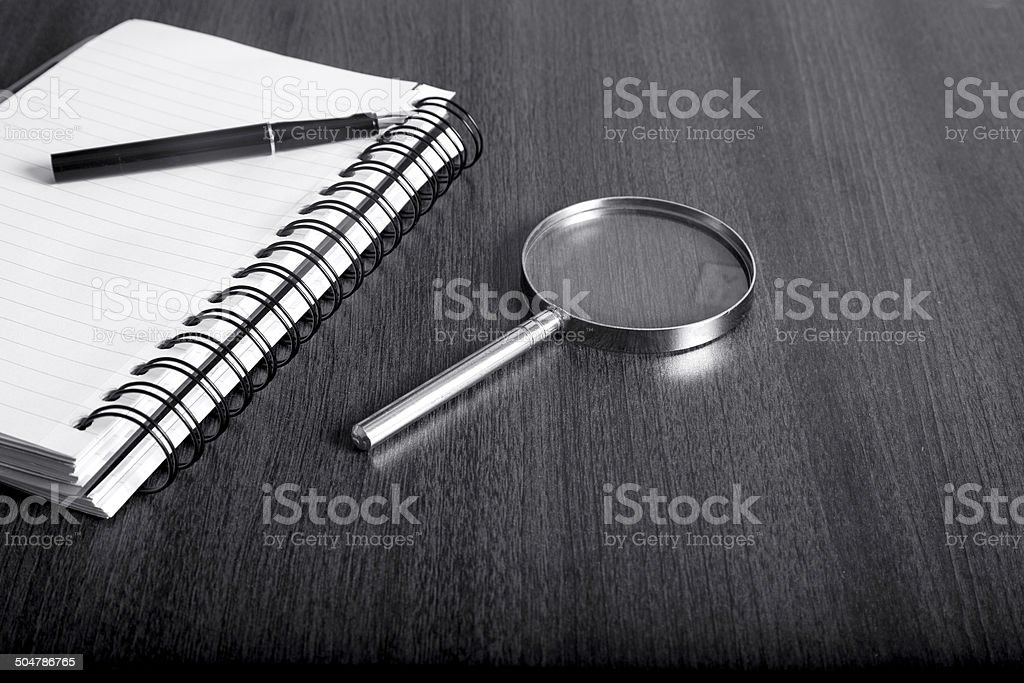 Notebook and magnifier on wood table stock photo