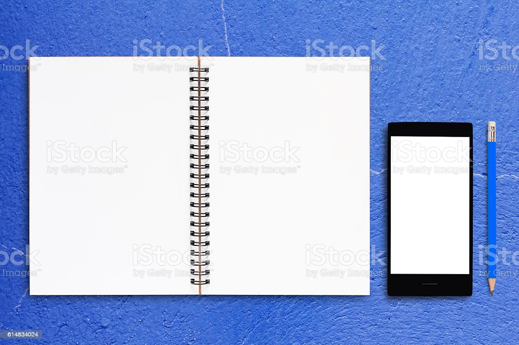 Notebook and Mobile Phone on Blue Background stock photo