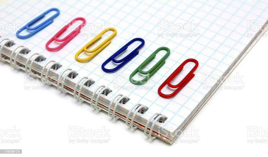 Notebook and multi-coloured paper clips. royalty-free stock photo