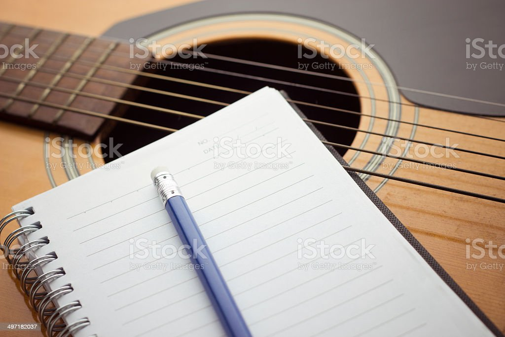 Notebook and pencil on guitar royalty-free stock photo