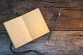 notebook and pencil on old wooden table.