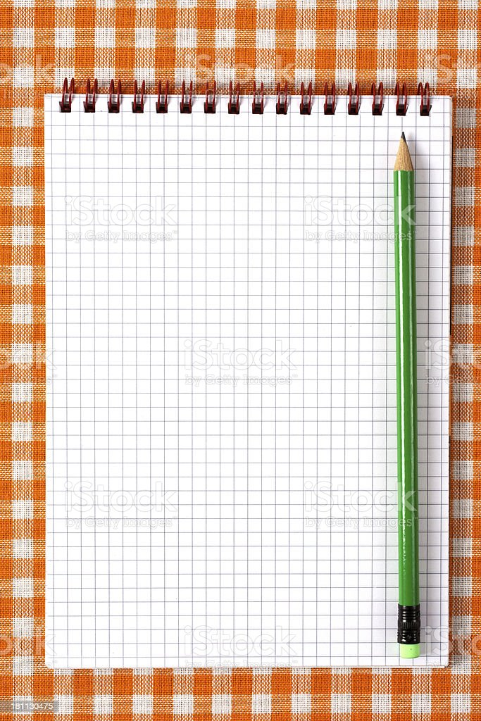Notebook and pencil on orange tableclot royalty-free stock photo