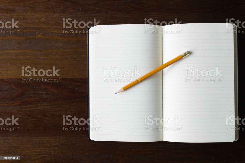 Notebook and pencil on wood table stock photo