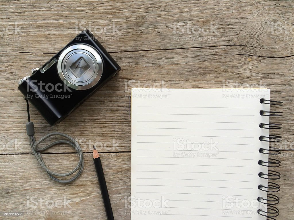 Notebook and pencil on wooden table background textured with camera. stock photo