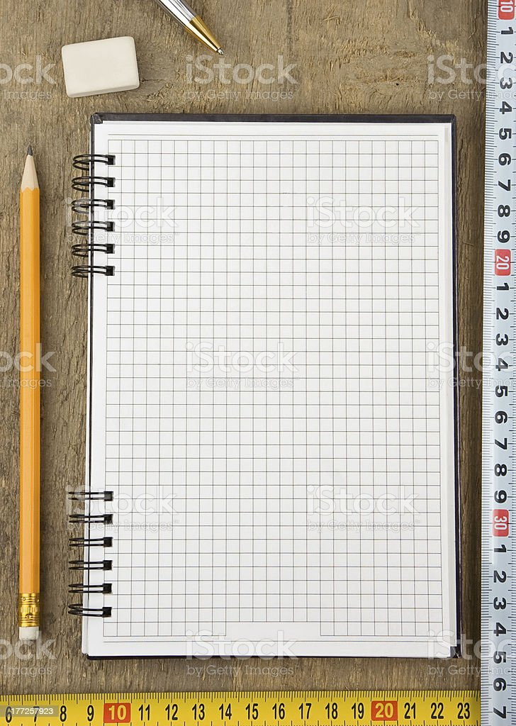notebook and tape measure on wood royalty-free stock photo
