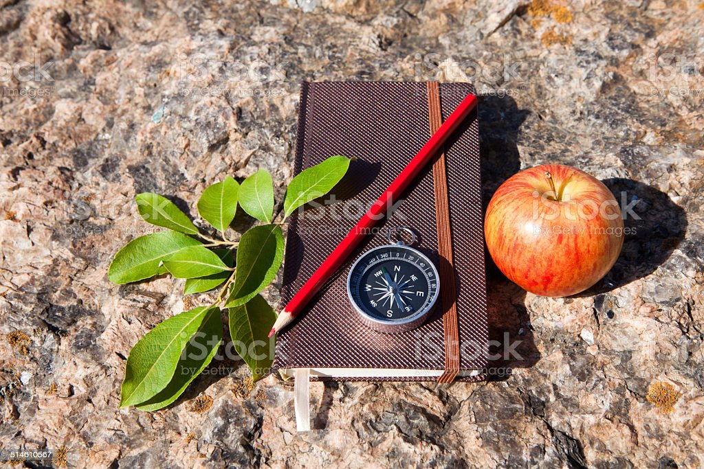 Notebook, compass, apple on stone background stock photo