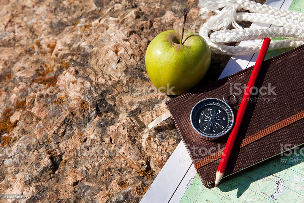 Notebook, compass, apple, rope on stone background stock photo