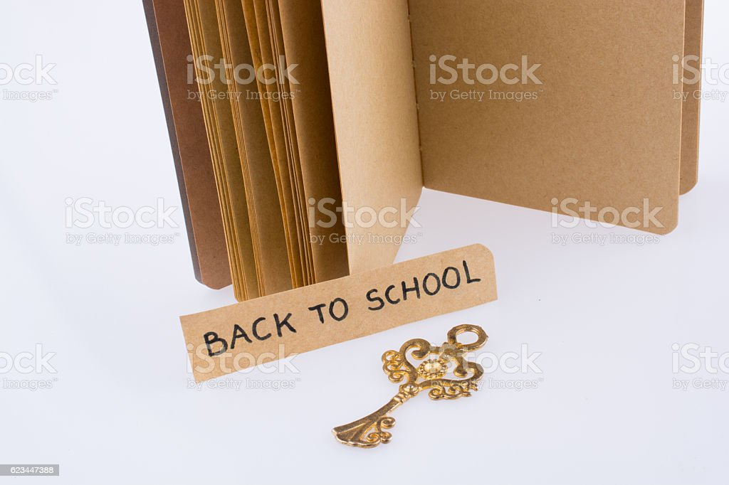 Notebook, key and back to school title stock photo
